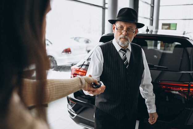 Stary człowiek odbiera klucze od samochodu w salonie samochodowym
