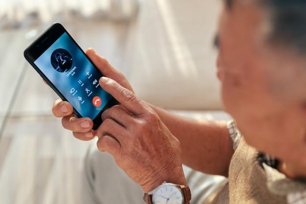 Stary człowiek odebrał połączenie z nieznaną osobą przez inteligentny telefon w domu, telefon oszustwa na starszej osobie.