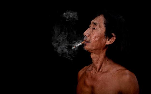 Stary człowiek palił na czarnym tle obraz dymu papierosowego rozprzestrzeniał się w koncepcji ust