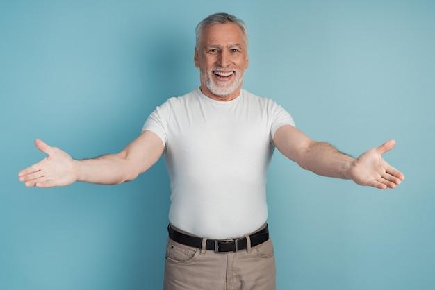 Stary człowiek patrząc na kamery, uśmiechając się z otwartymi ramionami do uścisków.