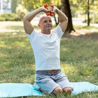 Stary człowiek pracujący na matę do jogi w przyrodzie