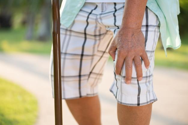 Stary człowiek siedzi na kanapie i ma ból kolana, uraz kolana w parku.