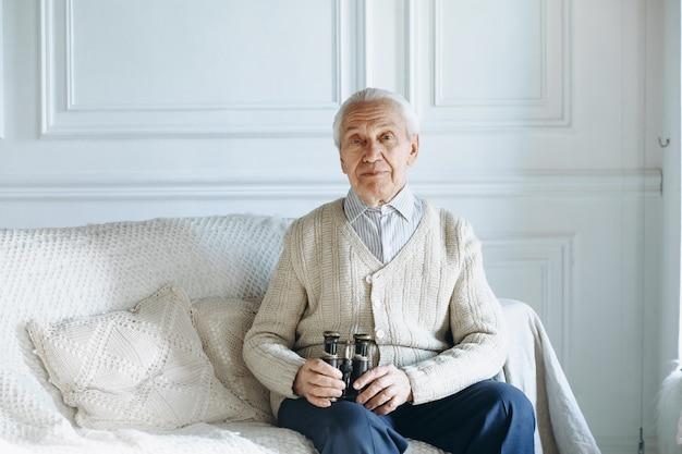 Stary człowiek siedzi na kanapie