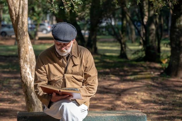 Stary człowiek siedzi na ławce, czytając książkę