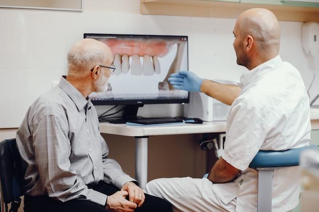 Stary człowiek siedzi w gabinecie dentysty
