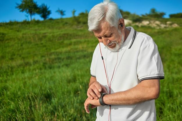 Stary człowiek sprawdza czas podczas outdoors sportów aktywności.