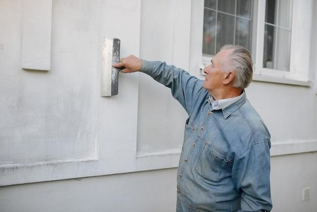Stary człowiek stoi blisko budynku z remontowymi narzędziami