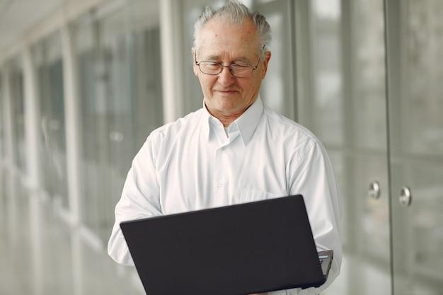 Stary człowiek stojący w biurze z laptopem
