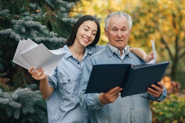 Stary człowiek stojący w parku backround z wnuczką