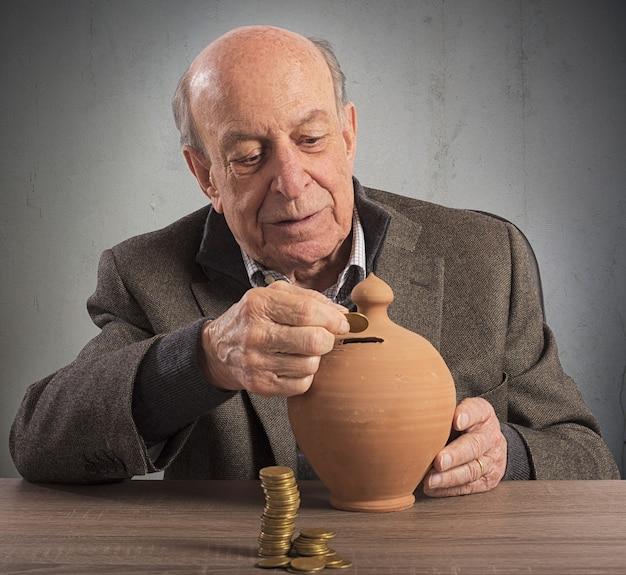 Stary człowiek trzyma emeryturę w skarbonce