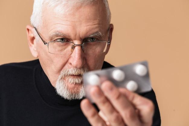 Stary człowiek trzyma tabletkę z portretem tabletki