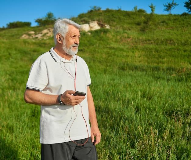 Stary człowiek trzyma telefon, działa na wsi.