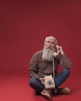 Stary człowiek trzyma telefon