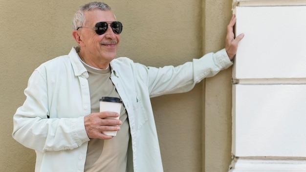 Stary człowiek trzymający filiżankę kawy