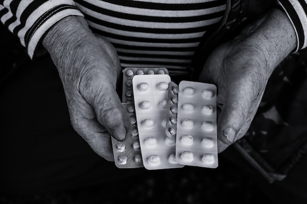 Stary człowiek trzymający pigułki w rękach