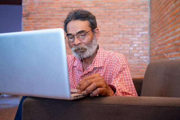 Stary człowiek uczy się korzystać z laptopa w domu, starszy mężczyzna korzysta z komputera w domu