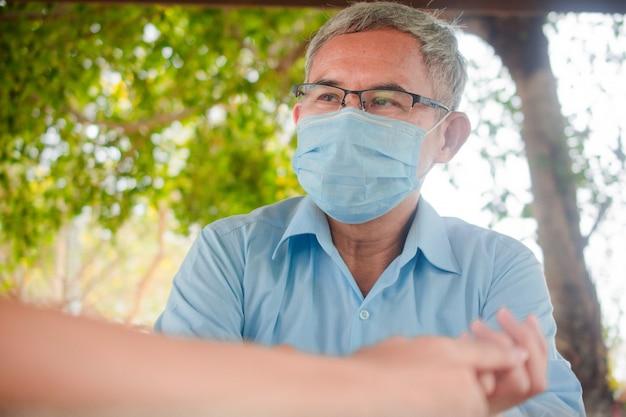 Stary człowiek używa maski do ochrony przed wirusem corona 19 podczas komunikacji z ludźmi