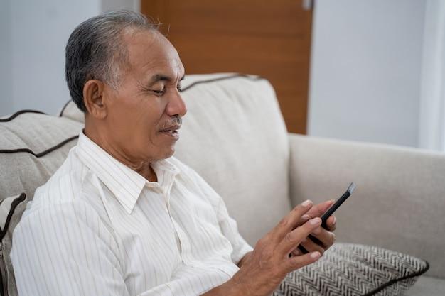Stary człowiek używa smartphone w domu
