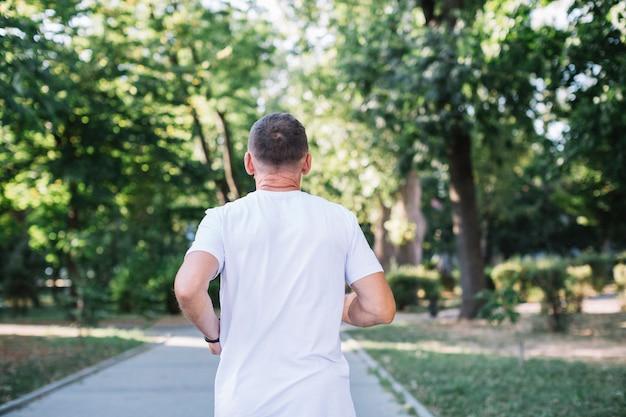 Stary człowiek w białym tshirt biega w parku