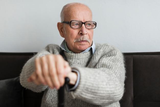 Stary człowiek w domu opieki z okularami i laską