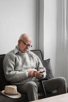 Stary człowiek w domu opieki za pomocą smartfona