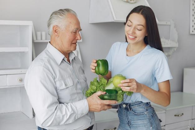 Stary człowiek w kuchni z młodą wnuczką