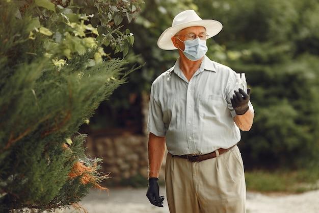 Stary człowiek w masce medycznej. mężczyzna w parku. motyw koronawirusa.