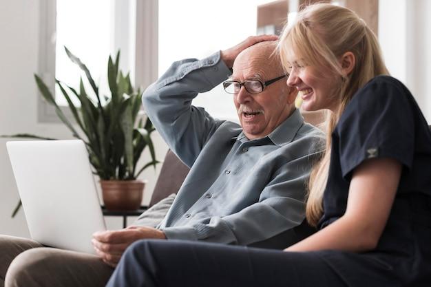 Stary człowiek wideo dzwoni do rodziny z domu opieki z pomocą pielęgniarki
