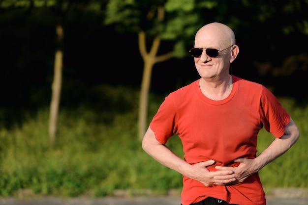 Stary człowiek z bólem brzucha w naturze
