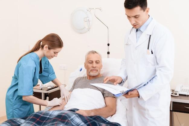 Stary człowiek z chorobą leży na łóżeczku w pokoju kliniki.