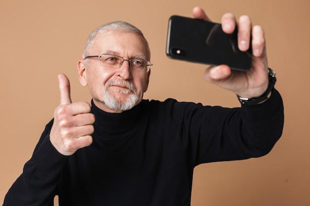Stary człowiek z portretem telefonu