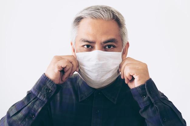 Stary człowiek z siwymi włosami pod maską zakrywającą usta i nos. koncepcja wirusa koronowego lub covid-19.