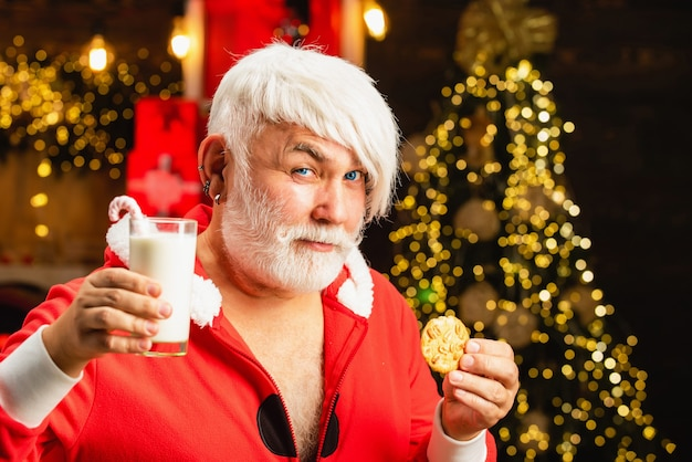 Stary człowiek z siwymi włosami w kostiumie santa trzymając mleko i ciasteczka