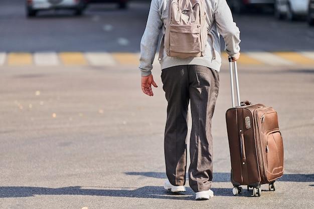 Stary człowiek z walizką na kółkach