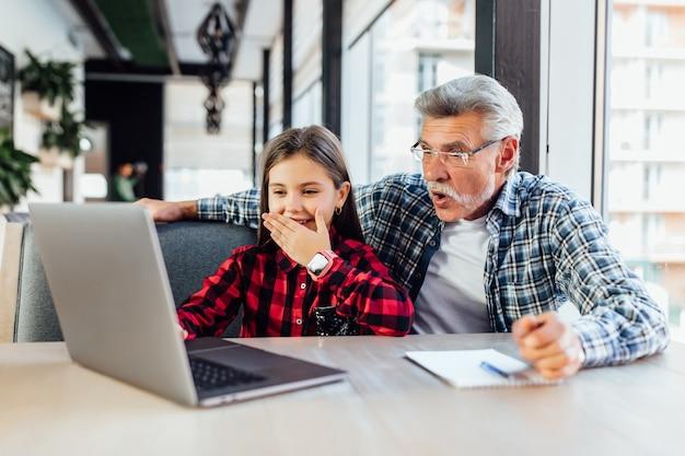 Stary człowiek z wnuczką za pomocą tabletu podczas rozmowy wideo z dzieckiem.