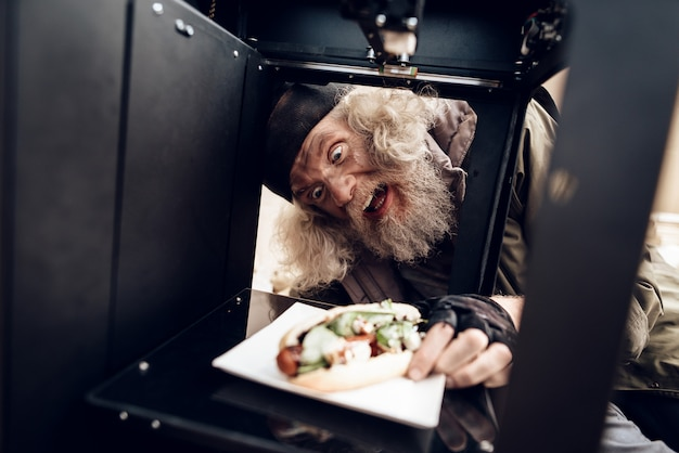Stary człowiek zrobił sobie kanapkę za pomocą drukarki 3d.