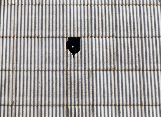 Stary dach z szarego łupka, pokryty pleśnią i porostami, część łupka jest wybita i jest dziura, przez którą spływa woda z deszczu