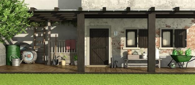 Stary dom z patio i sprzętem ogrodniczym