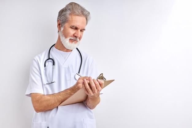 Stary, doświadczony kaukaski lekarz pisze objawy i diagnozuje
