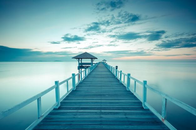 Stary drewniany bridżowy molo przeciw pięknemu zmierzchu niebu