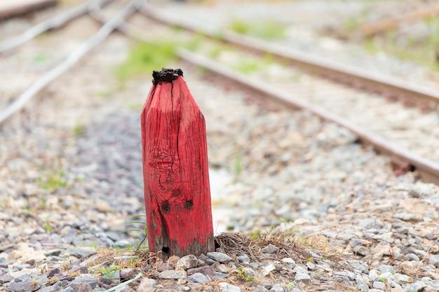 Stary drewniany czerwony filar dla ostrzegać w rozszczepionej linii kolejowej decyzi i kamienia milowego pojęciu