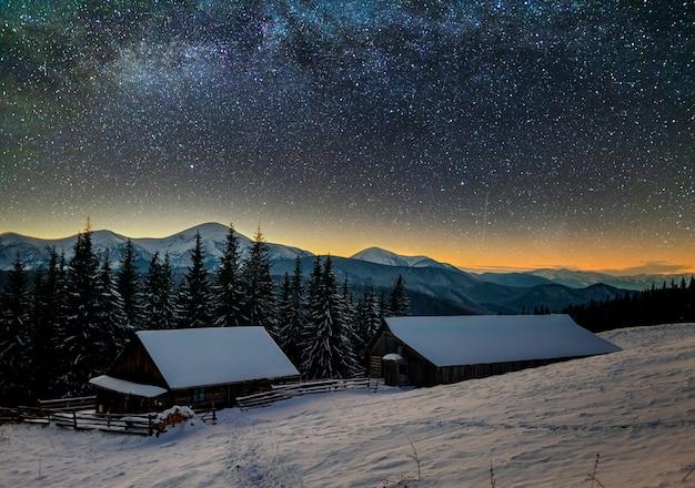 Stary drewniany dom, chata i stodoła, stos drewna opałowego w głębokim śniegu w górskiej dolinie, świerkowy las, zalesione wzgórza na ciemnym gwiaździstym niebie i droga mleczna. krajobraz górski zimowy noc.