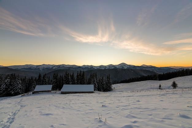Stary drewniany dom, chata i stodoła w głębokim śniegu w górskiej dolinie, świerkowy las, drzewiaste wzgórza na jasnym niebieskim niebie o wschodzie słońca. krajobraz górski zima panorama.