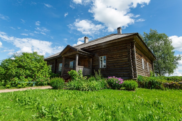 Stary drewniany dom rosyjski na zielonym trawniku latem.