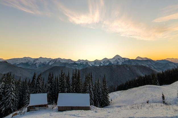 Stary drewniany dom w głębokim śniegu na górskiej dolinie