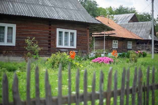 Stary drewniany dom wiejski w górzystym terenie w karpatach. tradycyjny budynek. podwórko z zieloną trawą.