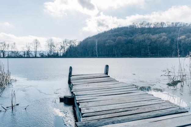 Stary drewniany molo na małym zamarzniętym kraju jeziorze w jesieni.