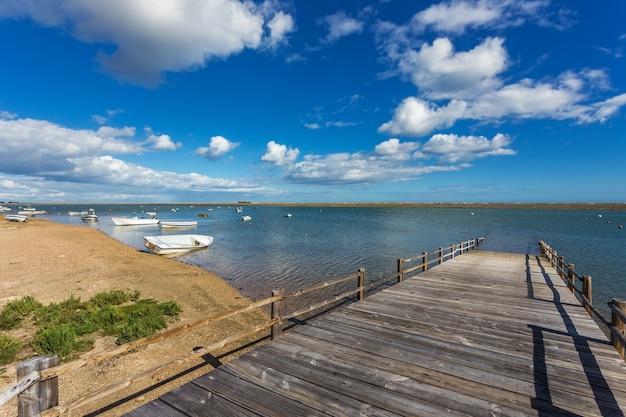 Stary drewniany most na zatoce i łodzie na wodzie. letni krajobraz.