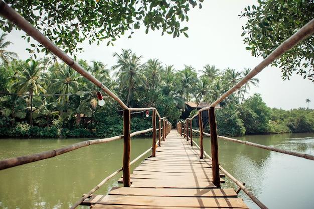 Stary drewniany most nad małą stawem lub rzeką, zamyka up. most dla pieszych nad rzeką, zielone drzewa.