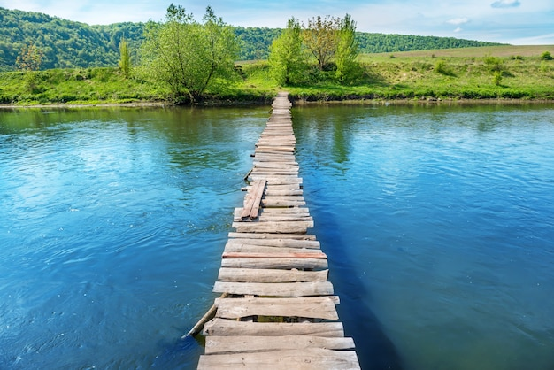 Stary drewniany most przez rzekę z zielonymi drzewami na brzegach